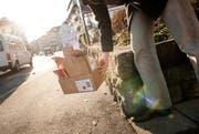 Ein Mann stellt in Luzern Karton auf die Strasse. (Bild: Roger Gruetter / Neue LZ)