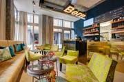 Der Loungebereich mit langem Sofa und vielen Kissen. (Bild: PD)