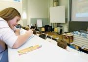 Kinder sitzen im Lesesaal der Pädagogischen Hochschule Zug und hören einen Vortag über Therapiehunde.
