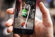 Das Spiel Pokémon Go findet per Einblendung von Monstern in das laufende Kamerabild statt. (Bild: EPA / Remko de Waal)