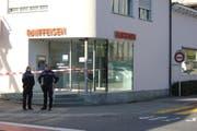 Zwei Polizisten überwachen die Raiffeisen-Filiale in Meggen. (Bild: Lucien Rahm (Meggen, 29. Dezember 2017))