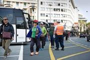 Eine Reisegruppe am Löwenplatz auf dem Weg zu ihrem Car. Überwacht wird das Ganze von einem Verkehrslotsen. (Bild Corinne Glanzmann)