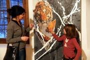 Zwei Besucherinnen schauen sich eine Collage von Werner Hoffmann an. (Bild Romano Cuonz/Neue OZ)