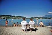 Zwei Retter der SLRG beobachten die Badegäste auf der Ufschötti in Luzern. Auch hier kamen schon Asylbewerber ums Leben. (Bild Pius Amrein)