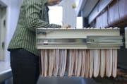 Eine Beamtin sortiert Akten im Steueramt. (Symbolbild) (Bild: Keystone)