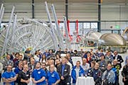 Blick in die neue Ruag-Raumfahrthalle 9 in Emmen gestern bei der Schlüsselübergabe, in der Mitte die Ruag-Aviation-Werksmusik. Hinten rechts «Vega»-Raketen-Formen aus Stahl, die als «Backformen» für die Fertigung der Raketenverkleidungen dienen. (Bild Pius Amrein)