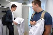 Pascal Portmann (links), angehender Fachmann Gesundheit, und Mattia Rüssi, der die Lehre zum Fachmann Betreuung absolviert, betrachten ihre Arbeitskleidung, bevor sie diese zum ersten Mal anziehen. (Bild Nadia Schärli)