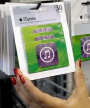 Customer picks up an Apple iTunes gift card on display at a Best Buy in Mountain View, Calif., Tuesday, July 17, 2012. (AP Photo/Paul Sakuma) (Bild: Paul Sakuma (AP))