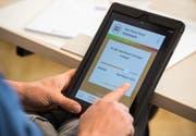 Ein Mann hält ein Tablet mit einer App zur Überprüfung von Fake News in den Händen. (Bild: Silas Stein / EPA)
