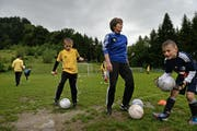 Hier wird bald auf Kunstrasen gespielt: Ruth Indergand vom Vorstand des FC Adligenswil mit Spielern der F-Junioren auf dem alten Fussballplatz. (Bild: Nadia Schärli)