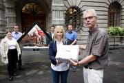 Yvonne Ruckli, Präsidentin der Jungfreisinnigen, übergibt Stadtschreiber Toni Göpfert die Unterschriften für den Erhalt der Kapellbrücke-Giebelbilder-Kopien. (Bild: Manuela Jans / Neue LZ)