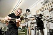 Thomas Theiler von Musikpunkt Gasser in Hochdorf repariert eine Posaune. (Bild: Corinne Glanzmann / Neue NZ)