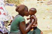 Die Frau ist Flüchtling aus Nigeria küsst ihr Kind in einem Transit-Camp. (Bild: EPA / STR)