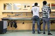 Zwei Asylsuchende an einem Waschbecken anlässlich der Einladung zum Tag der offenen Tür im vergangenen März in der Zivilschutzanlage in Dagmersellen, wo Asylsuchende untergebracht sind. (Bild: Keystone)