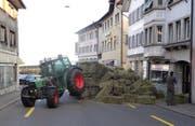 Ein Taktor in Schwierigkeiten: Sein Anhänger ist gekippt, Heuballen türmen sich auf der Strasse. (Bild: Kantonspolizei Schwyz (Arth, 7. April 2017))