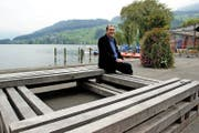 Jo Achermann sitzt im Sarner Seefeld auf seiner Installation aus Eichenbalken. (Bild Primus Camenzind)