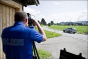 Ein Polizist misst die Geschwindigkeit vorbeifahrender Autos (Symbolbild). (Bild: Keystone)