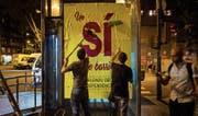 Spannungen programmiert: Separatisten schlagen in Barcelona Ja-Plakate an. (Bild: Emilio Morenatti/AP (28. September 2017))
