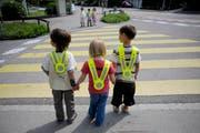 Schüler warten an einem Fussgängerstreifen, bis sie die Strasse gefahrlos überqueren können. (Symbolbild Pius Amrein)