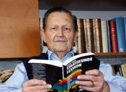 Alfred Huber hält seinen Bestseller in den Händen. (Bild Romano Cuonz/Neue OZ)