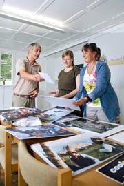 Klaus Bilang, OK-Mitglied, Szenografin Nina Bilang und Helferin Claudia Henggeler (von links) bereiten gemeinsam die Ausstellung im Haus am See in Unterägeri vor. (Bild Maria Schmid)
