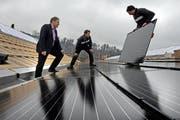 Rolf Hunkeler, Chef der 1a Hunkeler (links), bei der Installation der Fotovoltaik-Anlage auf dem Firmensitz in Ebikon. (Bild: Nadia Schärli / Neue LZ)