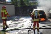 Die Einsatzkräfte der Schadenwehr Brunnen-Ingebohl löschen den Fahrzeugbrand. (Bild: Kantonspolizei Schwyz)
