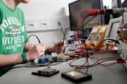 Ein Lehrling bei der Arbeit im Elektronik-Labor der Roche Diagnostics in Rotkreuz. Themenbild. (Bild: M. Christen/ Neue LZ)