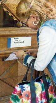 Eine Luzernerin wirft ihr Stimmcouvert in den Briefkasten beim Stadthaus in Luzern. (Bild: Eveline Beerkircher (17. Mai 2017))