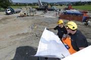 Zwei Bauarbeiter auf der Baustelle am Knoten Rigistrasse in Inwil studieren die nächsten Bauaktivitäten für die Tangente Zug/Baar. (Bild: Stefan Kaiser/ZZ)