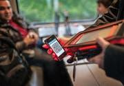 Eine Zugbegleiterin scannt ein elektronisches Ticket. (Bild: Keystone/Christian Beutler)