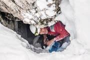Exkursionsleiter Pius Schnider schaufelt den Zugang zu einer Höhle unterhalb der Schrattenfluh frei. (Bild: Nadia Schärli (4. Februar 2018))