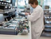 Produktion eines Stromzählers am Hauptsitz von Landis + Gyr in Zug. Bild: Gaetan Bally/Keystone (Zug, 3. August 2011)