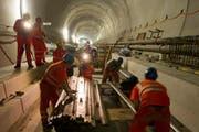 Arbeiter bewerkstelligen den Einbau der Bahntechnik im Gotthard-Basistunnel. (Bild: Keystone)