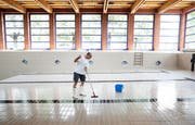 Bademeister Erwin Wöber schrubbt ausgiebig den Boden des Hallenbads Röhrliberg. (Bild Stefan Kaiser)