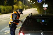 Ein Zuger Polizist kontrolliert den Ausweis eines Automobilisten. (Bild: Stefan Kaiser (Neue ZZ))
