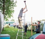 Es geht zur Sache auf dem Heitere: Christoph Bühler (links) hämmert mit Silvan Dober eine Holzstange in den Boden. Währenddessen werden weitere Utensilien auf das Gelände gekarrt (oben rechts) und das «böse Zäut» aufgebaut. (Bild: Roger Grütter (Zofingen, 8. August 2017))