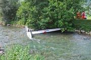 Der Flieger liegt in der Sarneraa und wird mit einem Seil gesichert. (Bild: Polizei Obwalden)