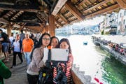 Chinesische Touristinnen machen ein Selfie auf der Luzerner Kapellbrücke. (Bild Roger Grütter)