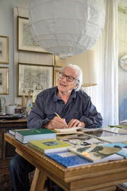 Seine Schriftzeugnisse füllen einen ganzen Tisch: Eduard Kloter (90) beim Signieren eines Buchs in seinem Zuhause in Meggen. (Bild Nadia Schärli)
