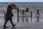 Eine Frau schützt sich mit ihrem Schirm vor Regen und Wind. (Symbolbild Georgi Licovski (Ohrid, 30. November 2017))