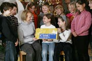 Schüler in Baar haben für die Weihnachtsaktion 2008 mit dem Verkauf von Engel 10'500 Franken gesammelt. Sie übergeben stolz den Geldcheck. Bild Philipp Schmidli/Neue LZ