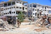 Syrische Soldaten patrouillieren in einem Quartier von Aleppo. Der Stadtteil wurde von den Rebellen vor kurzem zurückerobert. (Bild: EPA)