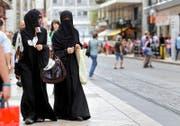 Gilt das Burkaverbot bald schweizweit? Zwei Frauen mit Kopftuch und Nikab, fotografiert in Genf. (Bild: Keystone/Salvatore Di Nolfi)