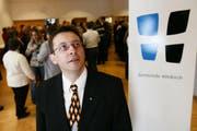 Hitzkirchs Gemeindepräsident Serge Karrer posiert neben dem Wappen der Gemeinde Hitzkirch, während die Anwesenden beim Apéro auf die Fusion anstossen. Bild Philipp Schmidli / Neue LZ