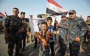 Irakische Sicherheitskräfte und Zivilisten feiern die gestrige Befreiung von Mossul. (Bild: Ahmad Al-Rubaye/AFP (Mossul, 9. Juli 2017))