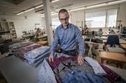 Roland Dobler begutachtet in seinem Geschäft in Willisau die Edelweisshemden, die seine Firma seit einigen Jahren in Portugal herstellen lässt. (Bild: Pius Amein / Neue LZ)