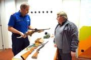 Kantonspolizist Peter von Flüe nimmt ein 30-jähriges Sportgewehr vom Alpnacher Armin Zumbühl entgegen. (Bild: Romano Cuonz / Neue OZ)