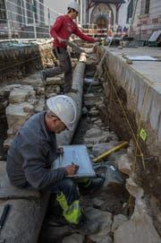 Die Archäologen Luca Winiger (hinten) und Andreas Christen graben die überreste der Mauer der alten Spitalkirche aus. Sie wurden bei der Strassensanierung in der Kleinstadt am Franziskanerplatz entdeckt. (Bild: Nadia Schärli (Luzern, 15. März 2017))