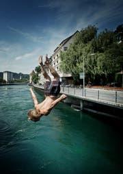 Die Hitze lockt Schwimmer in die Flüsse und verleitet viele dazu, von Brücken ins Wasser zu springen - so wie Dominik Furrer bei der Luzerner Spreuerbrücke. (Bild: Pius Amrein / Neue LZ)